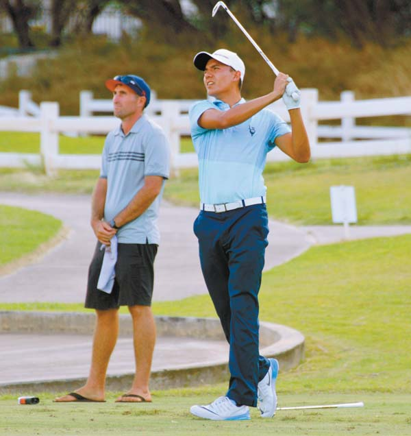 Alex Chiarella hits his drive off the 17th tee as caddie Jake Grodzinsky looks on during the final round of the Maui Open on Sunday at The Dunes at Maui Lani. The Maui News / ROBERT COLLIAS photo