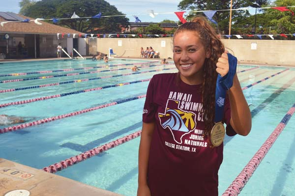 Jasmine O'Brien holds up the gold medal she won at the USA Swimming Futures Championships last week during a Hawaii Swim Club workout Wednesday at Kokua Pool in Kahului. The Maui News / ROBERT COLLIAS photo
