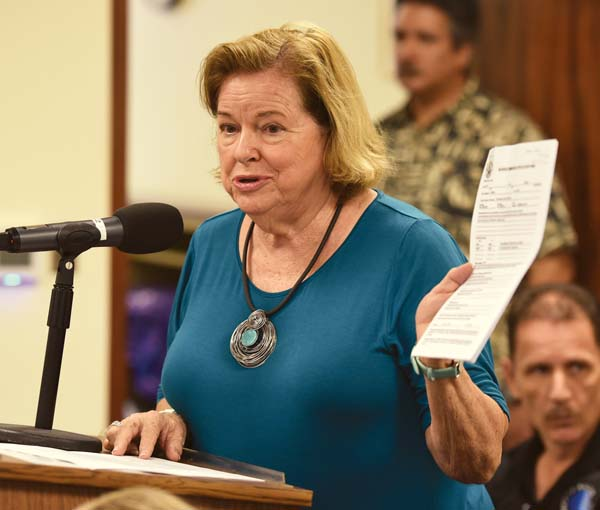 While testifying Wednesday morning, Madge Schaefer holds copies of the application forms Liquor Commissioners filled out for their posts, noting they did not need to undergo background checks or be fingerprinted. The Maui News / MATTHEW THAYER photo