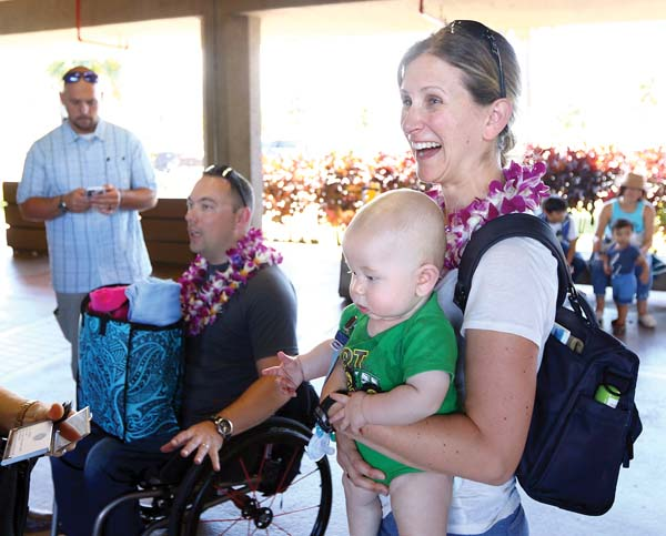 Tyler Wilson (from left), his wife, Crystal, and 5-month-old son, Matthew, speak to Maui veterans and county officials Thursday after arriving on the island for a vacation paid for by the nonprofit Vacations for Warriors. -- The Maui News / CHRIS SUGIDONO photo