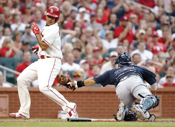 The Cardinals' Carlos Martinez scores as he avoids the tag from Braves catcher Kurt Suzuki in the fourth inning of St. Louis' 6-5 win over Atlanta on Saturday. -- AP photo