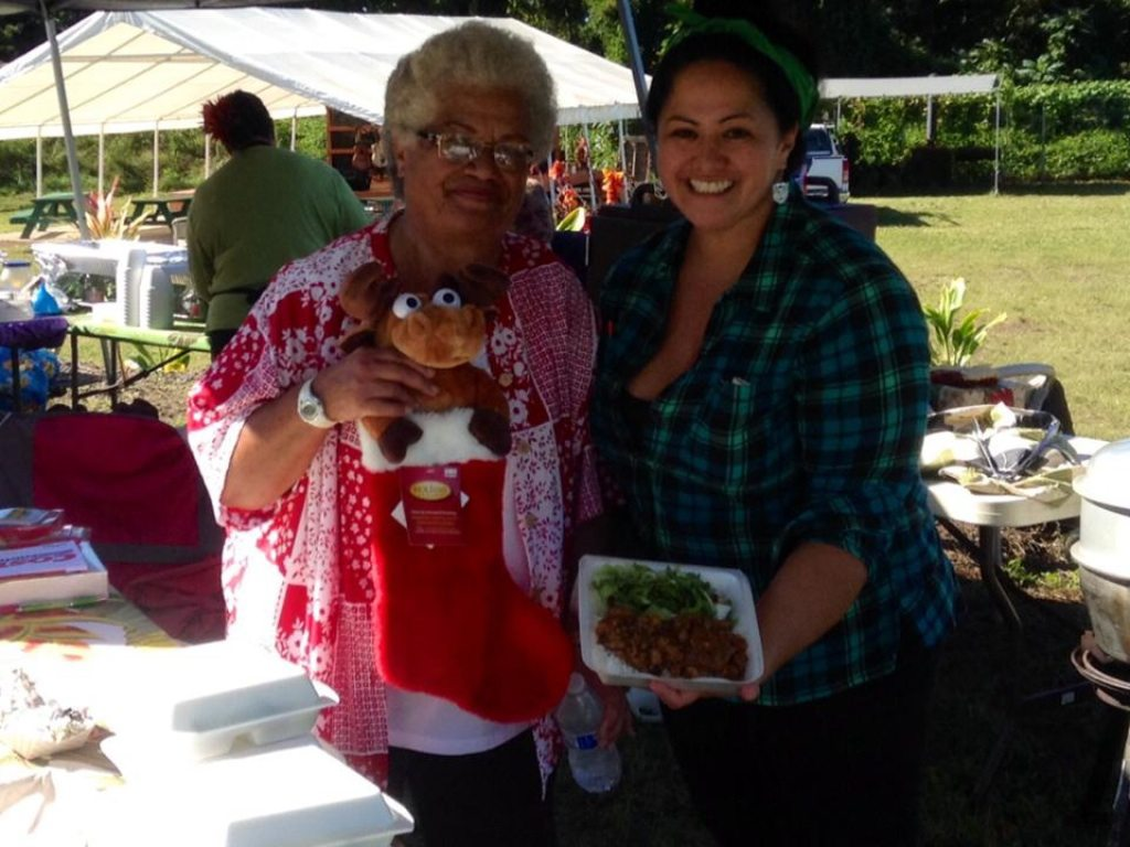 Saturday – Lynnette Kinney Sanchez and Kim Newhouse serve pastele-stew plate at Da Taste of Keokea; photo provided by organizing group.