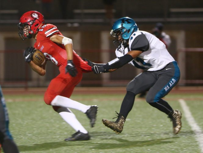 William Kai Bookland of Lahainaluna High School tries to break free from King Kekaulike's Arik Mendoza after catching a pass in the second quarter of the Lunas' 45-0 victory over Na Alii in the teams' Maui Interscholastic League opener Thursday night at Sue Cooley Stadium. • The Maui News / CHRIS SUGIDONO photo