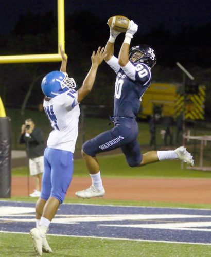 Nathan Facuri of Kamehameha Schools Maui catches a touchdown pass as Maui High's Torryn Kauhaahaa-Sulusi defends in the first quarter of the Warriors' 21-13 victory over the Sabers on Friday night at Kanaiaupuni Stadium. The Maui News / CHRIS SUGIDONO photo
