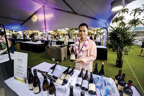 Master Sommelier Roberto Viernes pours fine wines to guests. -- Hawai'i Food & Wine Festival photo