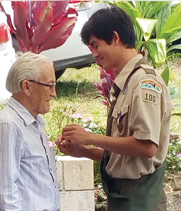 Aolama Chow pins the Mentor's Pin on Rich Kuykendall of Pukalani, Chow's piano teacher. In an Eagle Scout ceremony, the new Eagle Scout gifts the Mentor's Pin to someone who has most influenced his life.