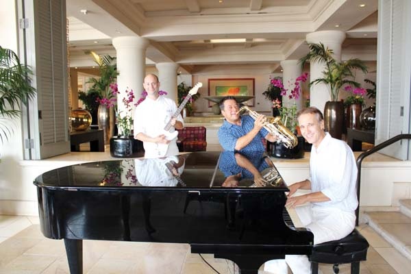Four Seasons Resort Maui Executive Chef Craig Dryhurst (left), strums the guitar, General Manager Jean Claude Wietzel tickles the keys on the baby grand (right) and Ken Martinez Burgmaier plays the saxophone in anticipation of the upcoming Maui Jazz & Blues Fest on Friday. Carla Tracy photo