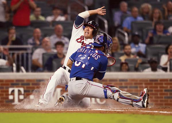 The Braves' Kurt Suzuki scores ahead of a tag by the Rangers' Robinson Chirinos during the second inning of Atlanta's 5-4 win over Texas on Wednesday in the second game of a doubleheader. AP photo