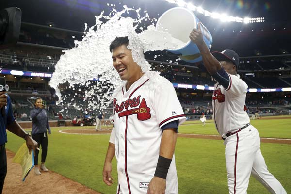 Kurt Suzuki is doused by Arodys Vizcaino during an interview after the Braves' win. AP photo