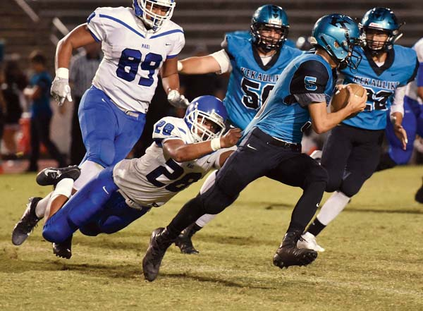 King Kekaulike's Trey Hunter fights to pull away from a diving tackle attempt by Maui High's Johnathan Aunese in the first quarter. -- The Maui News / MATTHEW THAYER photo