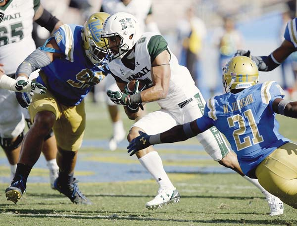 Hawaii's John Ursua looks for room to run between UCLA's Matt Dickerson and Mossi Johnson during the second half of the Bruins' 56-23 win over the Rainbow Warriors on Saturday. -- AP photo