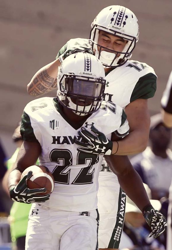 Diocemy Saint Juste celebrates with Rainbow Warriors teammate Keelan Ewaliko after a second-quarter touchdown. -- AP photo