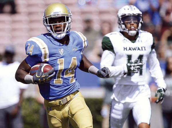 UCLA's Theo Howard scores in the first quarter as Hawaii's Manu Hudson-Rasmussen trails the play. -- AP photo