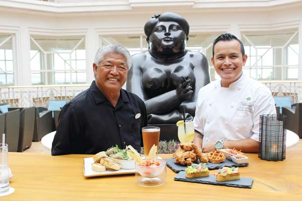 Longtime Botero Lounge mixologist Mich Domingo (left) and Grand Wailea Executive Sous Chef Jorge Gonzalez hang out at a high-top table with new menu items near one of several famous sculptures by Ferdinand Botero, after whom the bar is named. The Maui News / CARLA TRACY photo