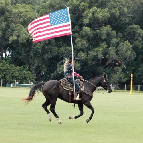 Kathryn Shields carries the American flag in for the national anthem during Maui Polo Club's opening day Sunday at Kaonoulu Ranch. Coral DeCoite photo