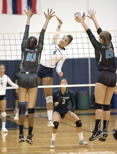 Kimani Fernandez-Roy of Kamehameha Schools Maui tries to get a shot past King Kekaulike's Lyric Love (left) and Brooklynne Albrecht during the second set of the Warriors' 23-25, 19-25, 25-14, 27-25, 15-8 win over Na Alii on Thursday at Kaulaheanuiokamoku Gym. The Maui News / MATTHEW THAYER photo