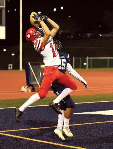 Lahainaluna High School's William-Kai Bookland pins the ball against his helmet on a touchdown reception as Tiliti Adams of Kamehameha Maui defends during the first quarter of the Lunas' 39-19 win over the Warriors on Friday at Kanaiaupuni Stadium. -- The Maui News / MATTHEW THAYER photo