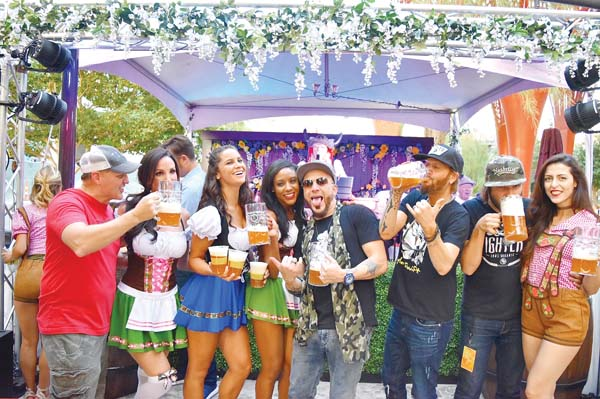 Bier! Bier! Bier! Ladies in dirndls and men in T-shirts and jeans clank steins of frothy brews at Oktoberfest at The Park in Las Vegas Sept. 28 to Oct. 1. -- MGM Resorts photo