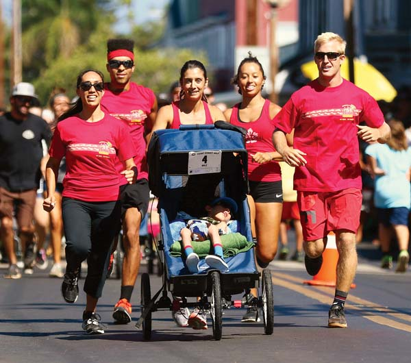 Team Hula Grill's (from left) Kaili Murbach, Rockett Isaiah, Lisa Kerrick, Akilah Curtis and Will Hawkes run with Murbach's 8-year-old son, Jeremy, on the way to winning the wheelchair division in 7:39. -- The Maui News / CHRIS SUGIDONO photo