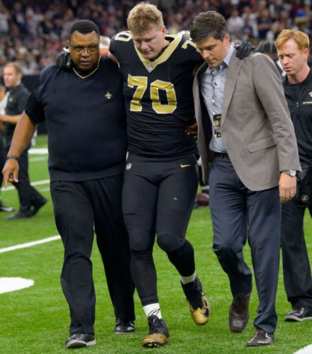 Mitchell Loewen of the New Orleans Saints is helped off the field during a game against the New England Patriots on Sunday. •New Orleans Advocate / MATTHEW HINTON photo