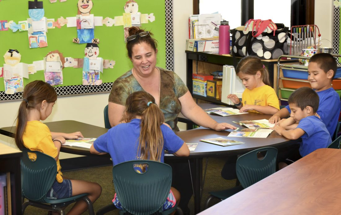 Makawao Elementary School teacher Alyssa Balderas Silva works on a reading exercise with 1st-graders Callie MacDonald (from left), Stormy Smith, Peter Ortiz-Calasa, Kala'ikeha Wong and Siena MacDonald on Wednesday afternoon during the school's after-school program. The school posted a 9 percentage point improvement in student achievement in English language arts/literacy from 2015 through 2017, according to the state Department of Education's Strive HI report. • The Maui News / MATTHEW THAYER photo