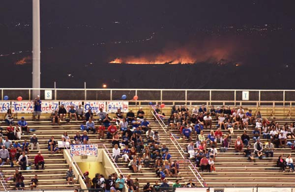Football fans at War Memorial Stadium watch a game Thursday night while a brush fire lights up Central Maui and blackens former sugar cane fields. The blaze was fully contained at 2:03 a.m. Friday. It consumed about 100 acres. A cause had not been determined as of Friday night. -- The Maui News / MATTHEW THAYER photo