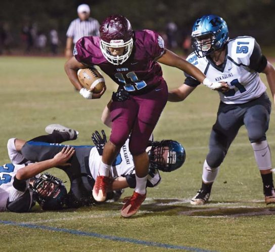 Baldwin High School's Bishop Wickes battles for extra yards as King Kekaulike's (from left) Rilee Peters, Caleb Crabtree and Kaleb Chun try to bring him down during the first quarter of the Bears' 55-6 win over Na Alii on Friday at War Memorial Stadium. -- The Maui News / MATTHEW THAYER photo
