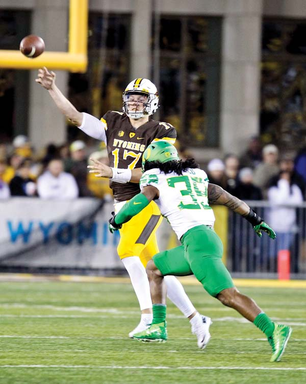 Wyoming quarterback Josh Allen throws a pass as Oregon linebacker Kaulana Apelu approaches during the Cowboys' 49-13 loss to the Ducks on Saturday. -- AP photo