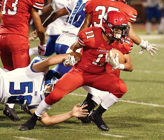Lahainaluna High School's Kamalei Watson tries to pull away from Maui High's Sione Aholelei during the first quarter of the Lunas' overtime victory over the Sabers on Saturday at Sue Cooley Stadium. -- The Maui News / MATTHEW THAYER photo