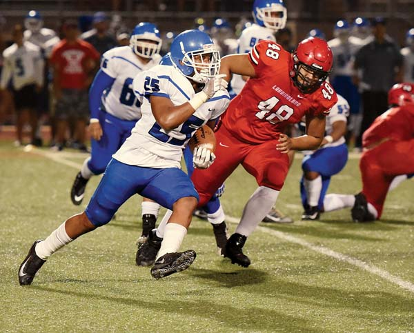 Maui High's Solomone Tongi carries the ball as Lahainaluna's Koa Evalu-Robinson gives chase in the second quarter Saturday. -- The Maui News / MATTHEW THAYER photo