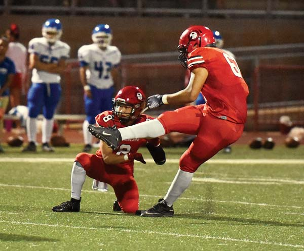 Lahainaluna's Pablo Rico kicks a first-quarter field goal out of the hold of Bailey Honda. -- The Maui News / MATTHEW THAYER photo