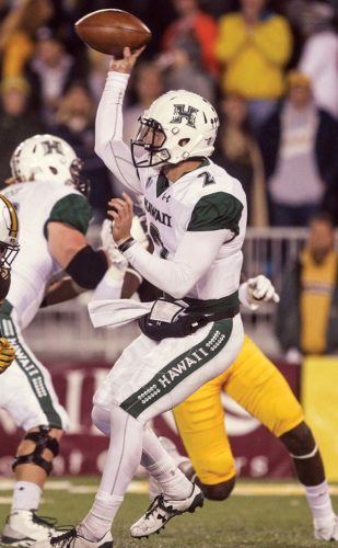 Hawaii's Dru Brown prepares to throw a pass during the first half of the Rainbow Warriors' 28-21 overtime loss to Wyoming on Saturday. -- AP photo