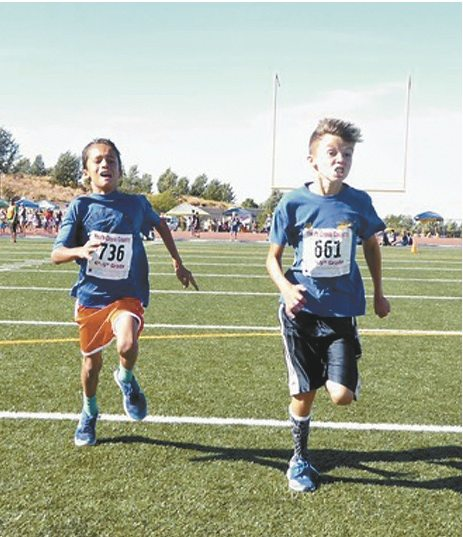 Dace Valenzuela of Makawao Elementary School beats Watkins Cooper of Pu'u Kukui to the finish line to win the boys 4th and 5th grade race in the Valley Isle Road Runners youth cross country championships Saturday at Kamehameha Maui in Pukalani.  • Valley Isle Road Runners / JIM LYNCH photo