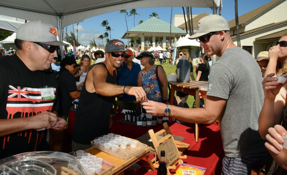 Mikey Kahinu of Na'ike's Shoyu Blend hands a sample of Molokai chili pepper and soy sauce to Jason Walker of Paia during last year's Made in Maui County Festival. Looking on is Mikey's brother Angel Kahinu. Na'ike's Shoyu Blend will again be participating in the Made in Maui County Festival on Nov. 3 and 4 at the Maui Arts & Cultural Center. • The Maui News / MATTHEW THAYER photo