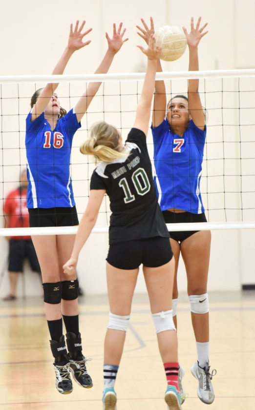 Seabury Hall's Ella Connor (left) and Isabel Bennett attempt a block against Maui Prep's Nicolette Falk during the second set of the Spartans' win over Na Pueo on Tuesday night at Erdman Athletic Center. • The Maui News / MATTHEW THAYERphoto