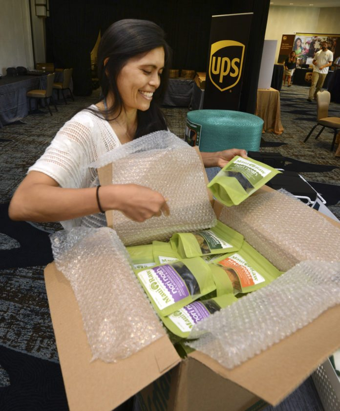 Maui Raw owner Michelle Valentin prepares a box of her products for shipping to Amazon's Fulfillment Center while taking part in Amazon's Liftoff program Tuesday afternoon at the Wailea Beach Resort – Marriott, Maui. The program is seeking small businesses to sell products on Amazon, the online retailing giant with 300 million active customer accounts. • The Maui News / MATTHEW THAYER photo