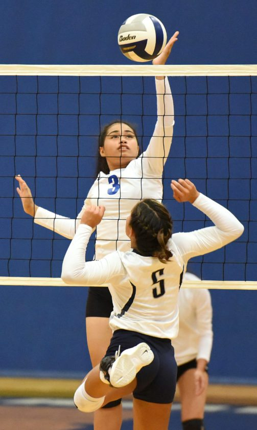 Maui High's Barbara Vakalahi tips a ball at the net against Kamehameha Maui's Aliah Ayau in the first set Thursday. • The Maui News / MATTHEW THAYER photo