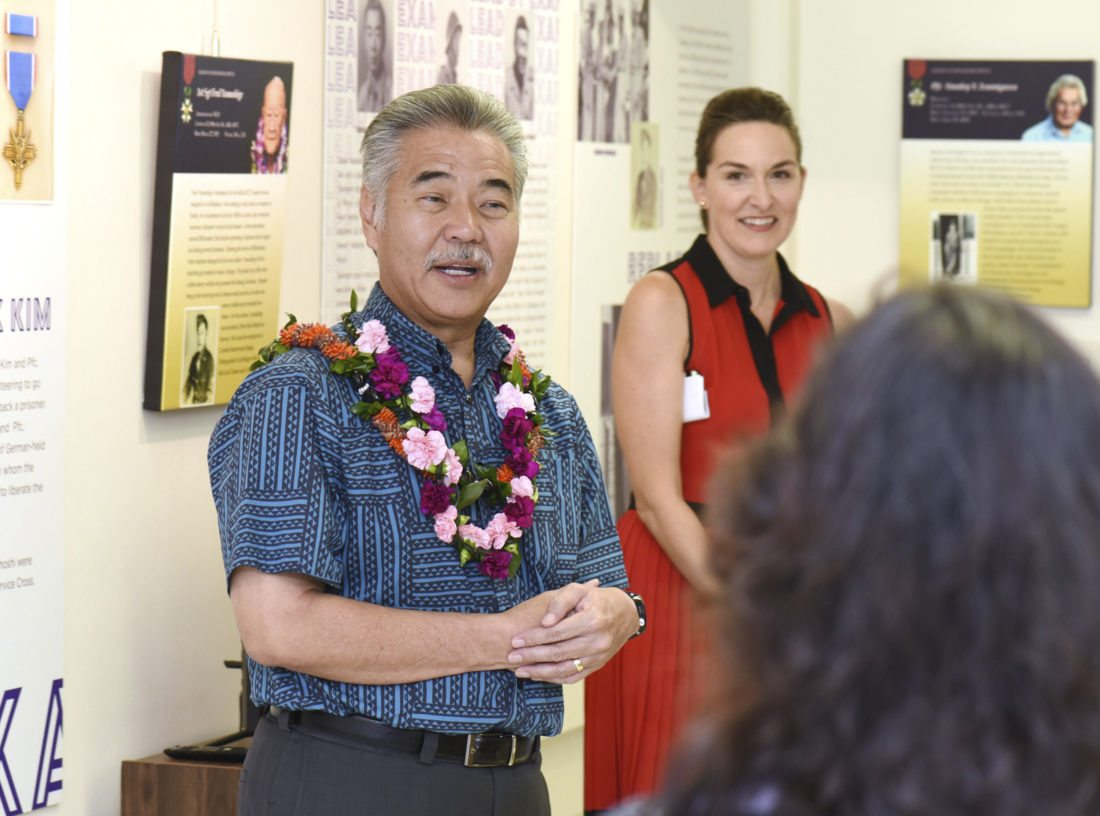 """Gov. David Ige speaks to Nisei Veterans Memorial Center board members and supporters during a tour of the """"One Puka-Puka: The Purple Heart Battalion"""" exhibit Thursday. Looking on is center Executive Director Deidre Tegarden. Ige paid respect to the bravery and sacrifices of the men of the 100th Infantry Battalion made during their bloody campaigns in Europe, but he said much of their legacy was made by what they did when they returned to Hawaii. He credited their efforts to stop racism and inequality and the many contributions they made throughout the islands. •The Maui News / MATTHEW THAYER photo"""