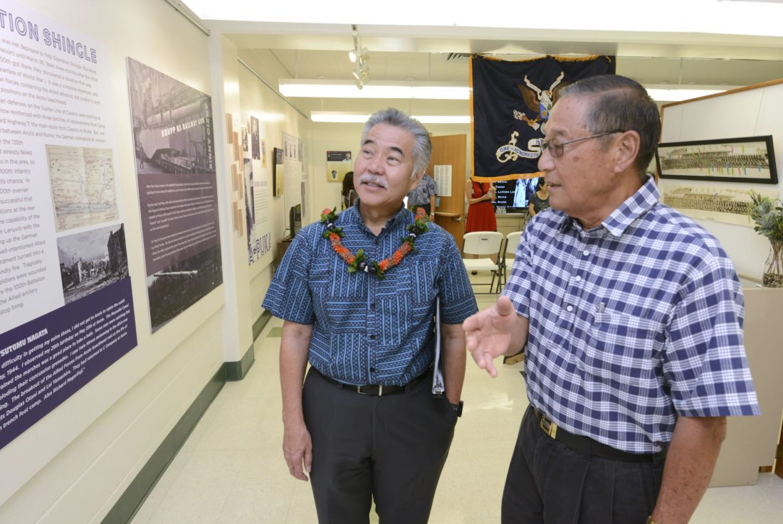 """Gov. David Ige (left) receives a tour of the Nisei Veterans Memorial Center's summer exhibit titled """"One Puka-Puka: The Purple Heart Battalion"""" from center board member David Fukuda on Thursday morning in Wailuku. The men's fathers served together in the 100th Battalion's A Company during World War II. They were Maj. Mitsuoshi Fukuda and Pvt. 1st Class Tokio Ige. The highly decorated 100th Infantry Battalion was formed 75 years ago, almost entirely of nisei, or second-generation Japanese, from Hawaii six months after the attack on Pearl Harbor. Along with touring the Education Center, Ige visited the facility's Maui Adult Day Care and Kansha Preschool. Later, he spoke at the Maui Chamber of Commerce's annual governor's luncheon at the King Kamehameha Golf Club. •The Maui News / MATTHEW THAYER photo"""