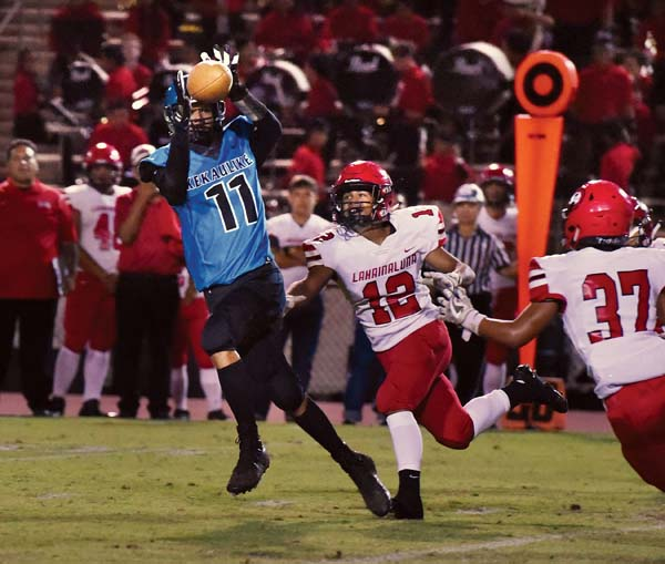 Na Alii's Arik Mendoza catches a pass as the Lunas' Jesse Dudoit (12) and Zeff Dudoit defend during the first quarter. -- The Maui News / MATTHEW THAYERphoto