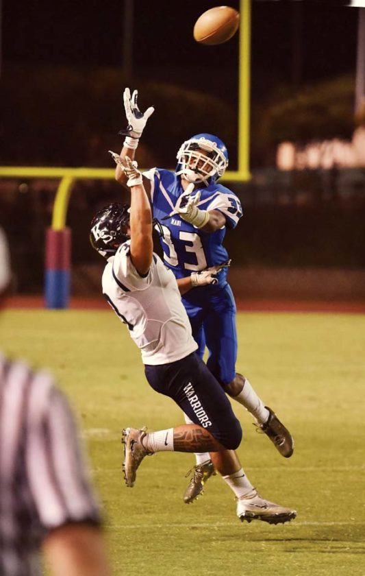 The Sabers' Spencer Takitaki defends a second-quarter pass intended for the Warriors' Kiha Mossman.  -- The Maui News / MATTHEW THAYER photo