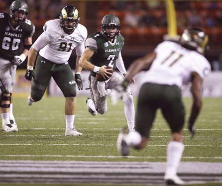 Hawaii quarterback Dru Brown is pursued by Colorado State's Jakob Buys as the Rainbow Warriors' Cris Posa trails the play during the second quarter of the Rams' 51-21 win Saturday at Aloha Stadium. -- AP photo