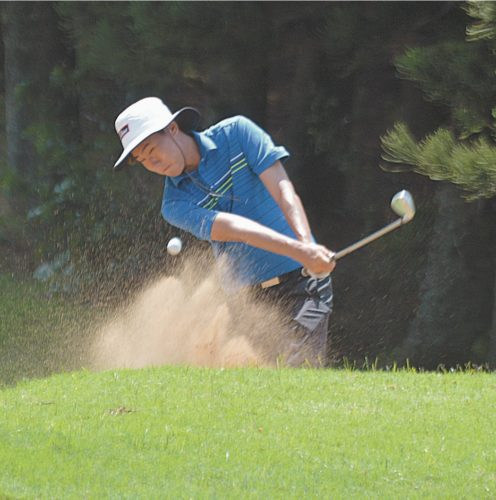 Chad Lee hits out of a bunker on the Kapalua Bay Course's 18th hole Sunday's while competing in the boys 15-18 division of a Hawaii State Junior Golf Association Junior Tour Series event.  • The Maui News / ROBERT COLLIAS photo