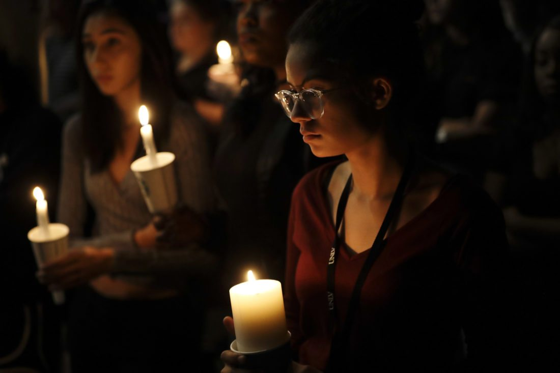 Natalynn Rivis (right), a student at the University of Nevada at Las Vegas, takes part in a vigil Monday on the campus for the victims of Sunday's shooting. • AP photo