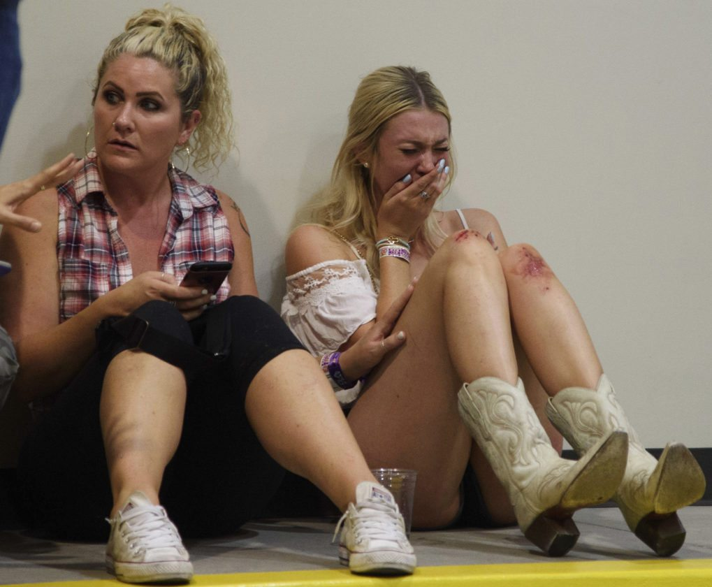 A woman cries while hiding inside the Sands Corp. hangar after Sunday's shooting at the Route 91 Harvest Festival in Las Vegas. • AP photo