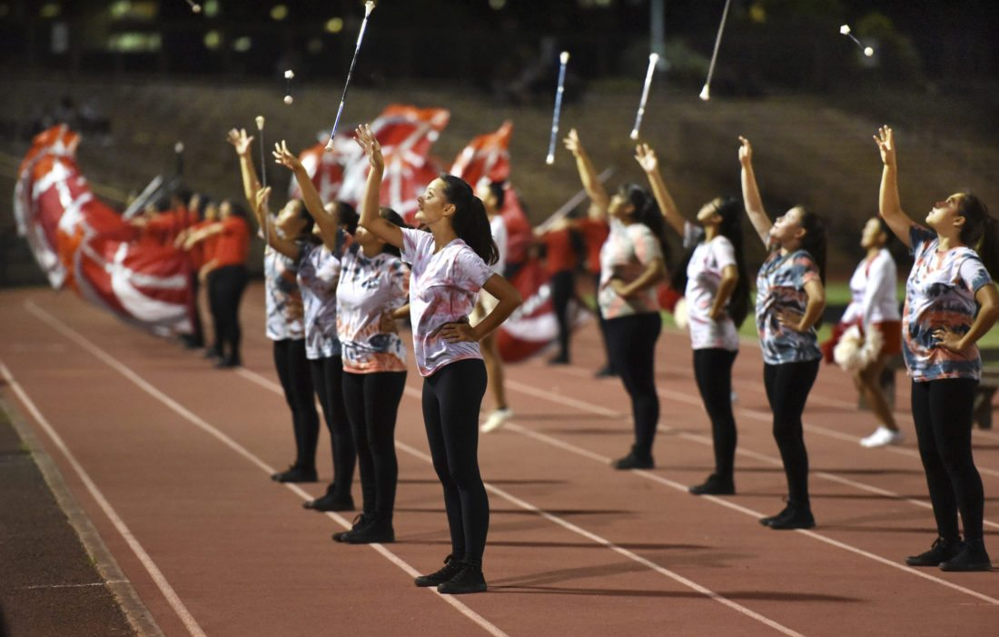 Lahainaluna High School majorettes and color guard members join the band and fans in celebrating a touchdown during Friday night's 52-0 win over King Kekaulike High School at War Memorial Stadium in Wailuku. The majorettes are the only students tossing and twirling batons in the Maui Interscholastic League. Band Director Myron Carlos said that he didn't know if any other schools in the state had twirlers but that the University of Hawaii Band has one. Lahainaluna's band and auxiliary numbers 120 students. Jon Shigaki is the assisting staff member. •The Maui News / MATTHEW THAYER photo