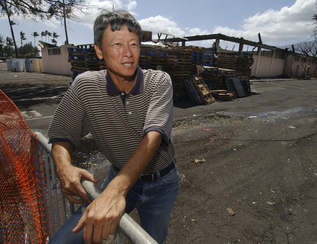 Ah Fook's Supermarket President Raymond Hew stands in front of what was left of his business after a fire on Feb. 27, 2005, at the Kahului Shopping Center. The market moved into its corner spot at the shopping center in 1955. Hew relocated the market into a smaller spot at the shopping center. Ah Fook's has been sold to Michele Pomroy Fraser, whose family owns and runs Kahului Carpet & Drapery. • The Maui News / MATTHEW THAYER photo