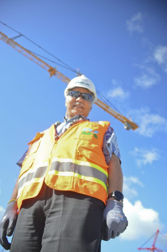 "Gov. David Ige stands in front of a towering construction crane Thursday at Kahului Airport. He said construction crews were making ""tremendous progress"" on the airport's new $340 million consolidated rental car facility. • The Maui News / BRIAN PERRY photo"