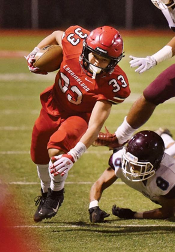Joshua Tihada carries the ball for Lahainaluna High School in a 17-14 overtime win over Baldwin on Friday at Sue Cooley Stadium. -- The Maui News / MATTHEW THAYER photo