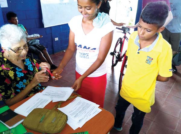 Charlotte Flavin, one of the founders of Somos Ohana Nicaragua, and a parent and student receiving a new bike in July sign the commitment contract for good attendance at the school built by the group in La Carreta, Nicaragua. -- MELE STOKESBERRY photo